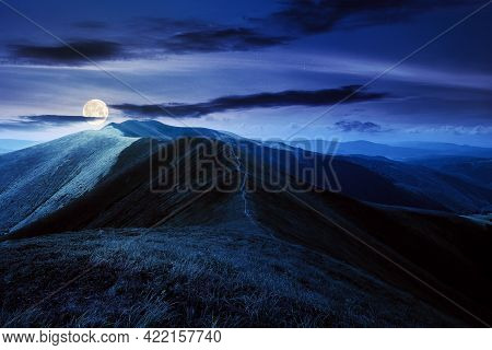 Mountain Landscape In Summer At Night. Grassy Meadows On The Hills Rolling In To The Distant Peak In