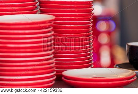 Lots Of Empty, Red Ceramic Plates Stacked In Piles. Clean Dishes Prepared For Self-service. Close-up