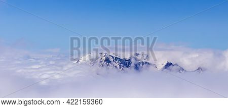 A Picturesque, Natural, Minimalist Landscape With A Mountain Peak Above Dense Low Clouds. The Top Of