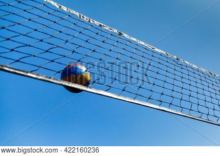 Volleyball Ball Flying Over The Volleyball Net On A Blue Summer Sky Background. Summer Leisure Activ