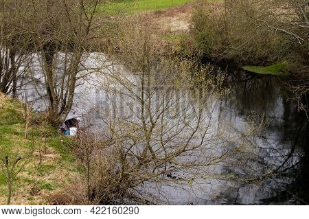Beautiful River Art A Rural Area In Galicia. Aged Woman Washing Some Clothes On Its Waters.