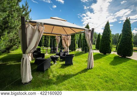 White Canvas Gazebo With Plastic Garden Furniture In A Summer Green Lawn
