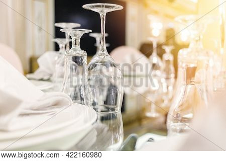 Close-up Of Festive Setting In Luxury Restaurant. Glasses, Plates, Cutlery On Mirror Table.