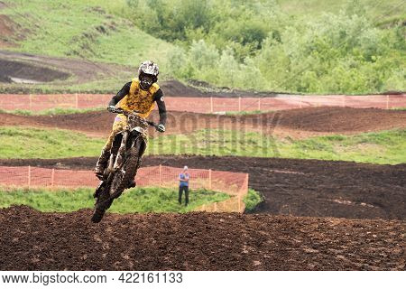 A Motorcycle Racer In A Jump On A Dirt Ring Track. It Rained. Rider Gear And Motorcycle In The Dirt.