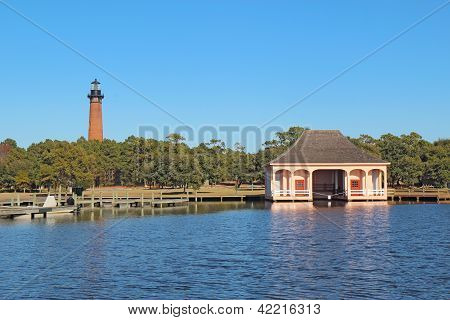The red brick structure of the Currituck Beach Lighthouse and the pink boathouse at Currituck Heritage Park near Corolla North Carolina poster