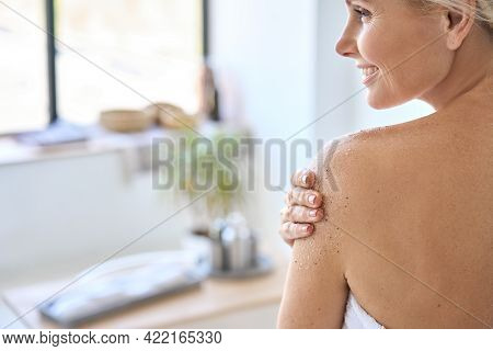 Back View Of Nude Beautiful Middle Aged 50s Woman Applying Exfoliating Peeling Sugar Scrub After Sho