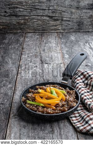 Teriyaki  Beef Mince With Paprika In Small Skillet On Wooden Table