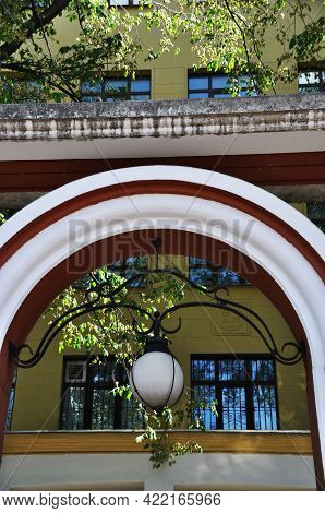 Arch Element With A Lantern. White Arch With A White, Round Lantern. Architecture.