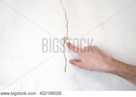 Construction Man Worker Repairing A Crack Wall Of A Home, Plastering Cement On Wall. Builder Applyin