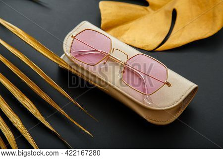 Pink Stylish Sunglasses On Color Dark Black Background With Gold Palm Leaves. Fashionable Trendy Col