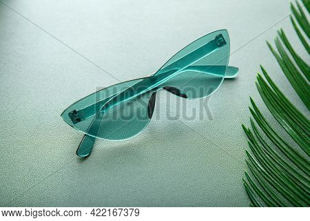 Stylish Green Sunglasses. Bright Summer Sunglasses On Green Background With Palm Leaf. Fashionable L