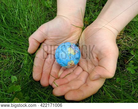 Planet Earth In Hands On A Background Of Green Grass. Ecology. Environmental Protection Concept