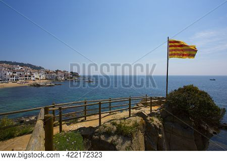 Calella De Palafrugell, Spain, May 1, 2020 - Catalan Flag On Flagpole Over Sea. Pine Trees, Rocks An