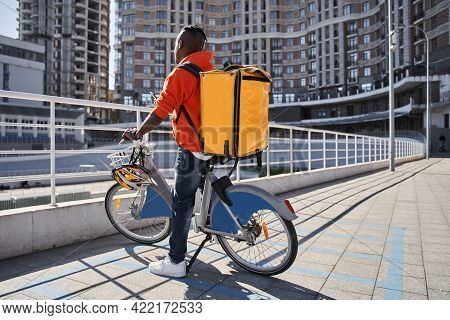 Delivery Courier Wearing Thermal Backpack Preparing To Rides At The Bicycle