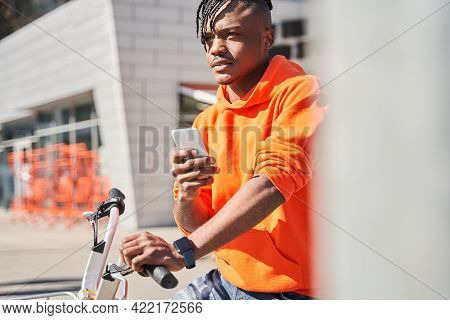 Courier Guy Checking Order Via Mobile Phone While Standing On City