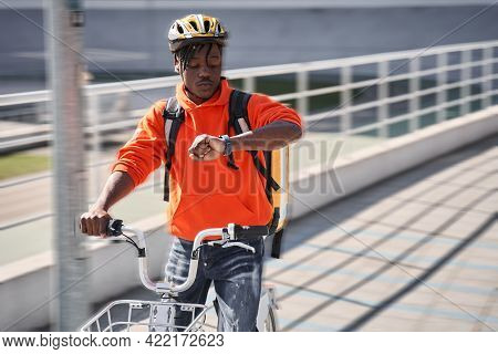 Guy Wearing Helmet And Sitting At The Bicycle Checking Time Via Smartwatch