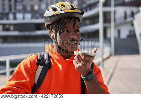Delivery Man Wearing Bicycle Helmet And Delivery Backpack Using Smartphone