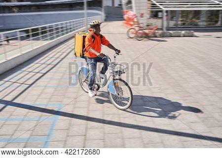 Delivery Man Wearing Red Sweatshirt And Yellow Delivery Backpack Sitting At The Bicycle