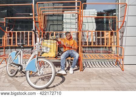 Food Supplier Sitting At The Station At The Street Near His Bicycle And Termo Backpack