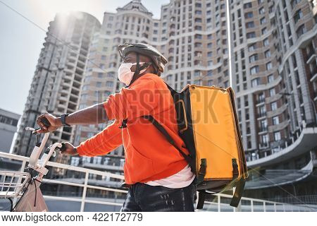 Man Wearing Protective Mask Riding At The Bicycle While Making Food Delivery