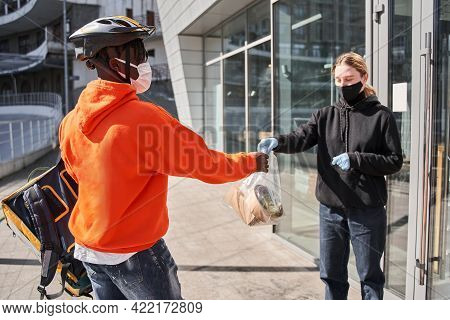 Male Courier Giving A Paper Bag With The Food To His Client At The Street