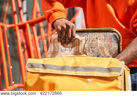 Courier Taking Paper Bag With Food Of The Yellow Bag While Standing At The Street