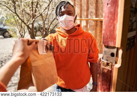 Customer Girl Taking Cardboard Bag From Courier In Protective Mask