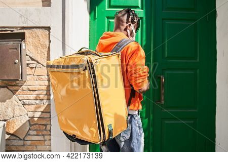 Courier Standing Is Under The Door And Holding Big Yellow Bag With Food