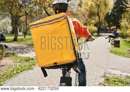 Courier With Yellow Backpack Riding At The Bicycle And Looking For A Way To The Client