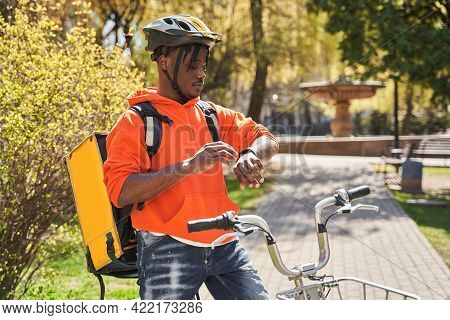 Courier Wearing Helmet Standing With Thermo Bag At His Bicycle