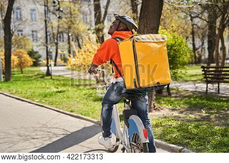Courier Wearing Thermal Backpack Rides At The Bicycle On The Road