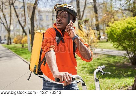 Delivery Courier Wearing Thermal Backpack Rides At The Bicycle On The Road