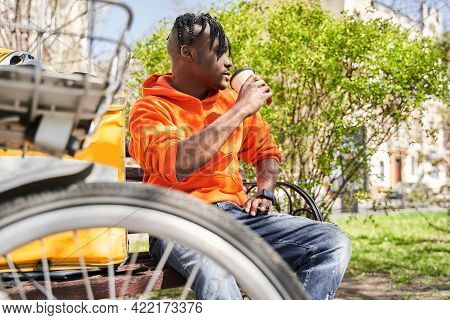 Man Drinking Coffee And Sitting At The Bench At The Street