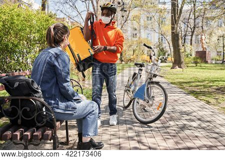 Courier Taking Off His Backpack Before The Giving Order To His Female Client