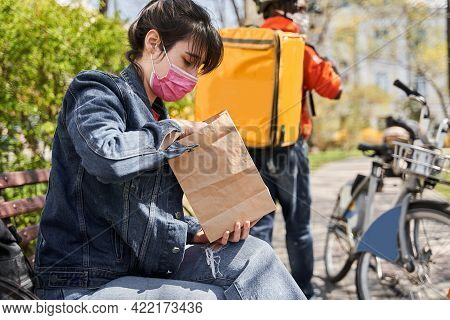 Client Woman Wearing Protective Mask Sitting At The Street And Holding Package