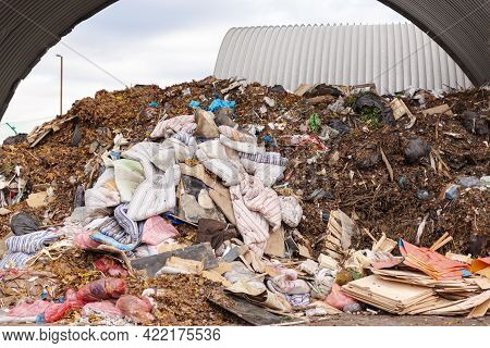 A Lot Of Mattresses In A Pile Of Garbage. A Large Pile Of Garbage In A Hangar At A Garbage Processin