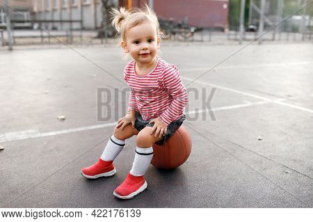 Little Girl Child Sits On A Basketball Ball And Looks Attentively And Smiles. Cute Baby Goes In For