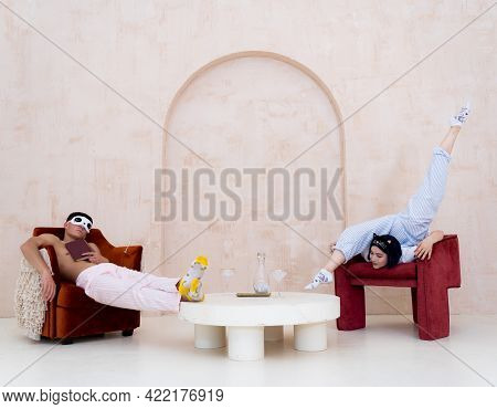 Couple In Pajamas Resting At Home By Creative Way. Concept Of Relationship, Creativity And Boredom