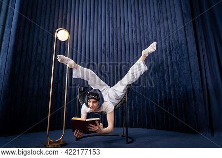 Flexible Young Girl In Pajamas Reading Book In A Creative Way Indoor . Concept Of Individuality, Stu