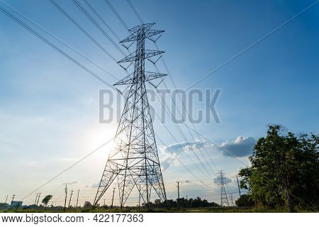 High Voltage Electric Transmission Tower, High Voltage Post, High Voltage Tower Near Sunset Blue Sky