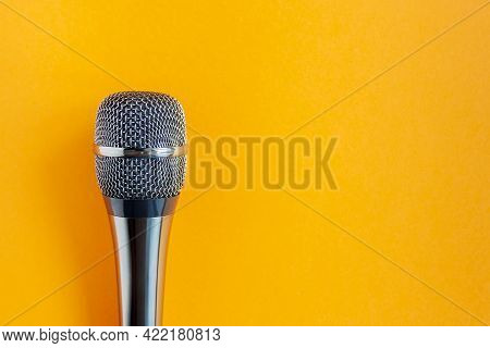 Microphone On A Colorful Orange Background Close Up. Singing, Writing Music, Karaoke Online, Creativ