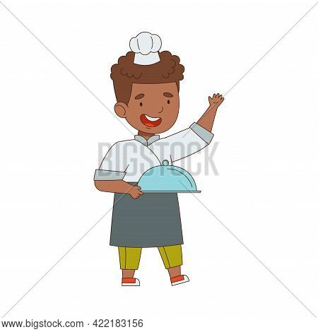 Little African American Boy Chef In White Toque And Jacket Holding Tray With Served Appetizing Meal