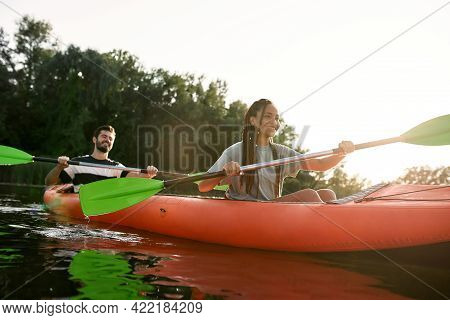 Happy Young Woman And Her Boyfriend Enjoying Kayaking Together In A Lake On A Late Summer Afternoon.