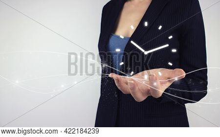 Time Management Concept. Hand Hold Digital Hologram Clock Time Symbol On Grey Background. Efficiency