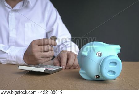 Businessman Holding A Coin At The Background With Focus On Piggy Bank Lying By The Side. Broke Or Fi