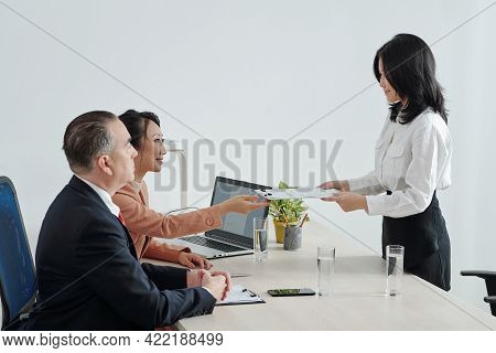 Smiling Young Job Applicant Giving Printed Curriculum Vitae To Hr Manager And Company Ceo Before Job