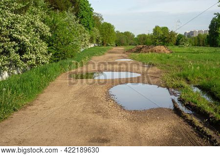 Suburban Dirt Road With Large Pits And Puddles. Along The Road There Is A Fence Overgrown With Bushe