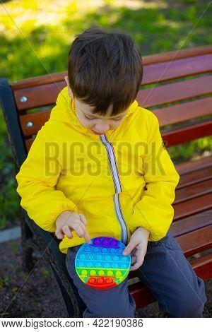 A Boy Plays An Anti-stress Pop It Toy . Baby And Pop It. Modern Toys. Anti-stress Toy. Motor Skills