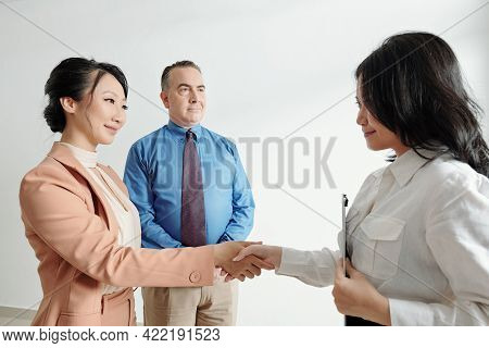 Friendly Smiling Business People Greeting And Shaking Hand Of New Coworker After Successful Job Inte