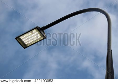 Led Street Lamp Glowing On Background Of Blue Sky With Clouds. Led Lights Saving Electrical Energy